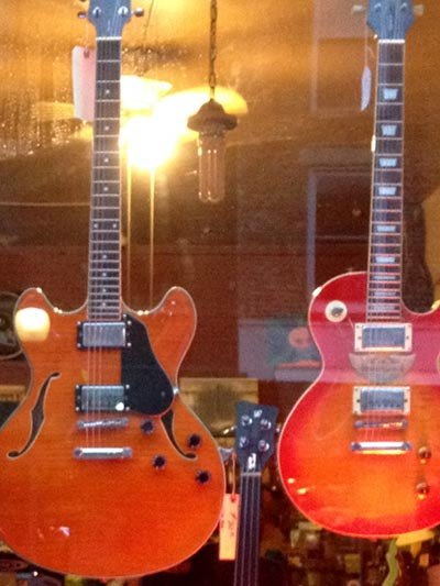 photo of two electric guitars in window